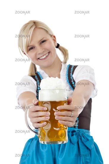 Junge blonde Frau im Dirndl prostet mit Masskrug zu