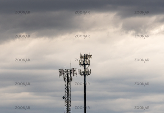 Two cellphone towers providing digital service to rural areas in cloudy skies