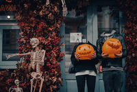 Headless couple holding pumpkin heads by the door on the street