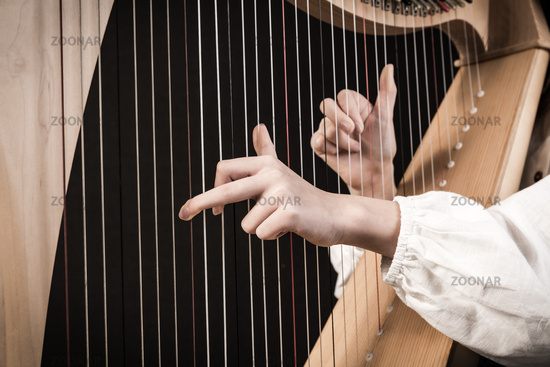 Hands playing wooden harp on black background
