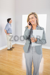 Smiling realtor calling someone with her mobile phone
