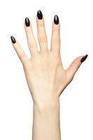 Female hand with black nails manicure isolated on white background.
