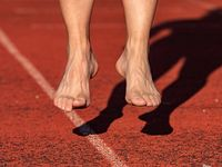 Middle aged barefoot jumping woman warm up calf muscles