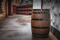 Wooden whiskey barrel in an alley with rows of barrels in background, Bushmills town