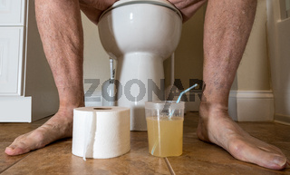 Senior adult man sitting on toilet with paper roll and colonoscopy prep in bathroom