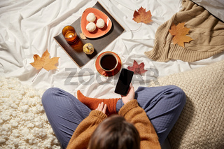 woman with smartphone at home in autumn