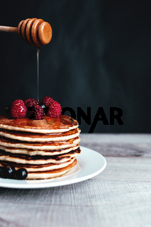 Juicy pancakes with berries and honey on a white plate, spoon, wooden table