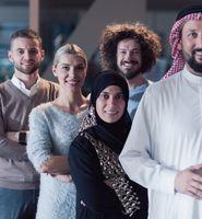 Portrait of multiracial diverse group of businesspeople team standing behind older Arab team leader