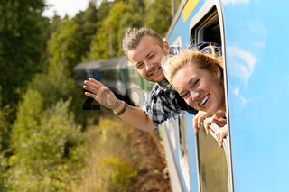Couple waving with heads out train window