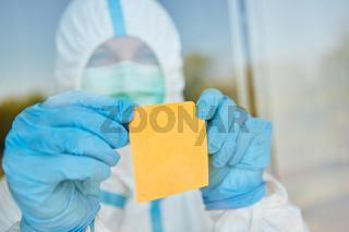 Gelber Haftnotiz wird angebracht an Tür oder Fenster von Klinik mit Arzt