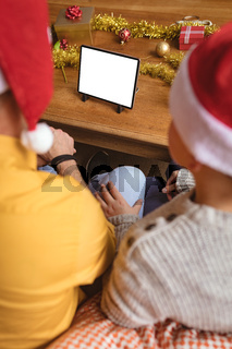 Father and two sons having a video call on digital tablet with copy space at home during christmas