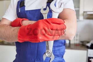 Handwerker mit Handschuhen hält Schraubenschlüssel