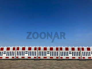 Road barrier. Red and white plastic construction fence. A large group of plastic barriers stands on the street pedestrian pavement during the construction of collapsed embankment in Dnipro, Ukraine
