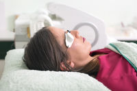 woman lying with protection glasses in beauty salon.