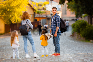 Young tourists family with their two lovely daughters