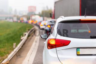 Cars waiting in traffic jam with illuminated brake lights