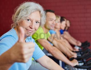 Seniorin im Fitnesscenter hält Daumen hoch