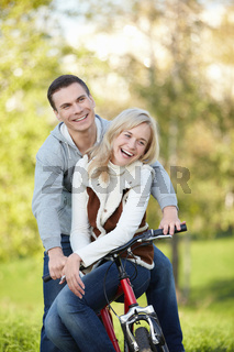 Laughing couple on a bike in the autumn park