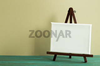 Easel with blank canvas on green wooden table. khaki wall background
