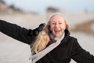 junge Frau läuft ausgelassen am Strand