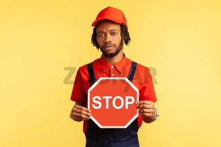 Handyman holding red stop sign, prohibitions, looking at camera with serious expression.
