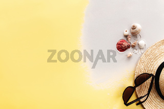 Summer background yellow flat lay with sand, shells, straw hat and sunglasses