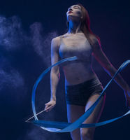 Woman exercising with ribbon in dust cloud view