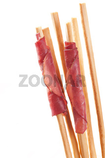 Grissini with ham isolated on white background