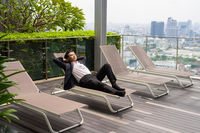 Asian businessman wearing suit and relaxing outdoors while laying down on sunbed in city