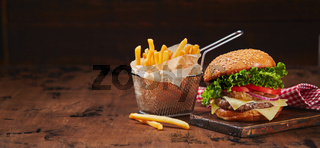 Homemade burger with beef, cheese and onion marmalade on a wooden board, fries in a metal basket. Fast food concept, american food
