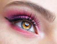 Closeup macro shot of human female eye with pink eyes shadows