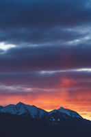 Alpine mountains with snow tops at sunset with dramatic red colored stormy cloudscape in Tirol, Austria