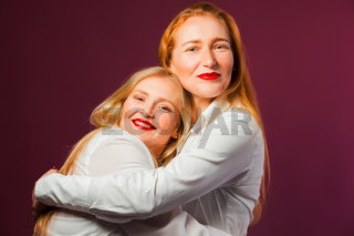 Young mother and adult daughter, studio portrait