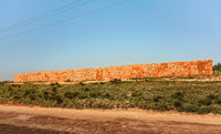 Orange red bricks made from local clay arranged in wide stack, ready for building a house near the road