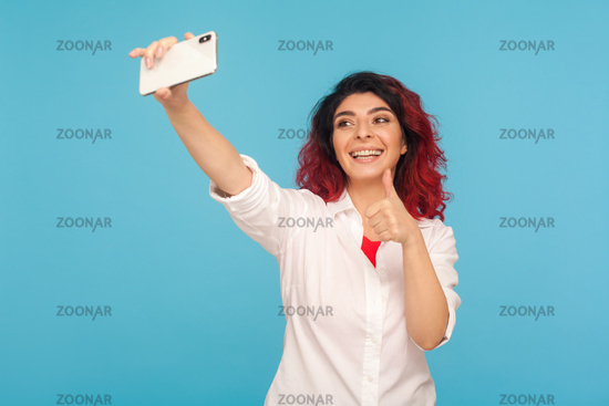 Portrait of emotional young woman on blue background.