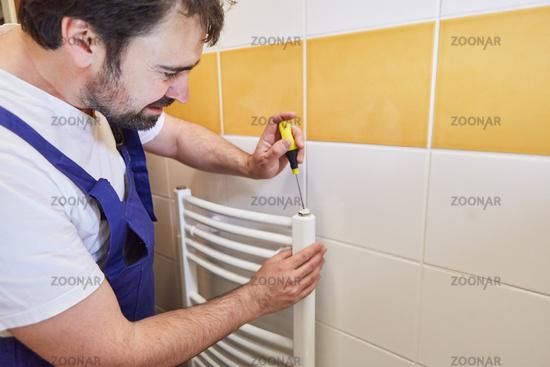 Installateur installiert Heizkörper von Heizung im Bad