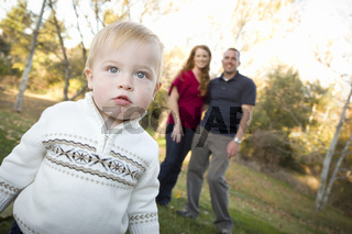 Cute Young Boy Walking as Parents Look On From Behind