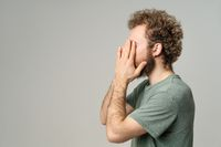 Tired or not getting enough sleep young man cover face with his hands. Lost face young man woke up in the morning man with curly hair in olive t-shirt standing sideways isolated on white background