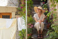 Beautiful female tourist wearing big straw sun hat and sundress sitting and relaxing on old stone house stairs during summer travel on Mediterranean cost on hot summer day.