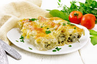 Cannelloni with curd and spinach in plate on board