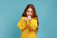 Angry little girl standing with raised fists, being ready to fight, looking with serious expression
