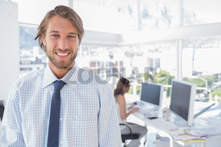 Smiling desginer standing in office
