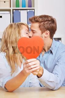 Paar küsst sich hinter rotem Herz