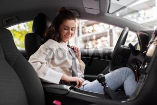 woman or female car driver fastening seat belt
