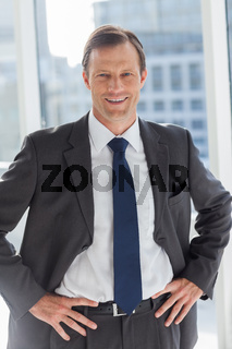 Smiling businessman with his hands on hips