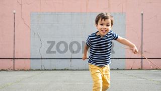 Little boy running towards camera on basque pelota court