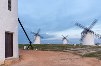 the whitewashed windmills of La Mancha in Spain under an evening sky with a full moon on the rise