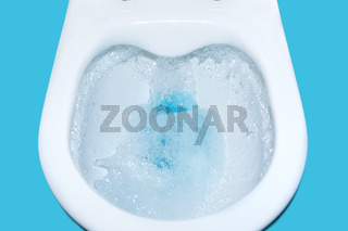 Toilet bowl flush with blue cleaning fluid isolated. cleaning Toilet close-up.