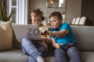 Two caucasian boys using laptop sitting on the couch at home