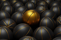 Many black basketballs with one golden basketball stands out